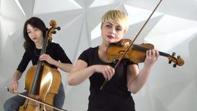 De muzikale kwartetmeisjes voert de samenstelling op drie violen en cello uit Witte studio stock footage