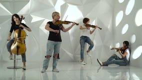 De muzikale meisjes van het koordkwartet voert de samenstelling op drie violen en cello uit Witte studio stock video