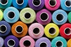 De naaiende draad in verschillende kleuren doorboort blauwgroen rood royalty-vrije stock foto