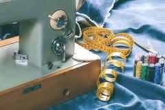 De naaiende jeans van het indigodenim met naaimachine, kledingstuk industrieel concept stock fotografie