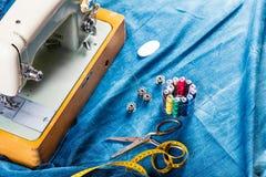 De naaiende jeans van het indigodenim met naaimachine, kledingstuk industrieel concept stock afbeeldingen
