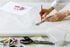 De naaister maakt patronen voor kleren Stock Afbeeldingen