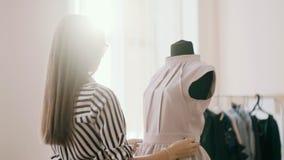 De naaister maakt de vouwen van de kleding recht en plakt een naald in de koker op de achtergrond, de zon die glanst stock videobeelden