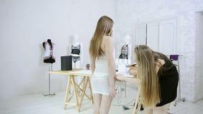 De naaister neemt metingen van ledenpop binnen atelier stock video