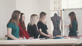 De naaister toont een groep meisjes hoe te om metingen op een model te nemen stock footage