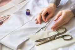 De naaister watteert ritssluiting aan een wit materiaal met purpere draad Stock Afbeeldingen