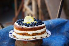 De naakte cake van de citroenbosbes met bosbessen op bovenkant en mascarpone het boter berijpen stock foto's