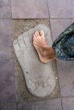 De naakte tribunes van het voetmeisje op de steenvoetafdruk Royalty-vrije Stock Foto's