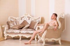 De naakte zitting van de machomens op retro stoel Stock Afbeeldingen