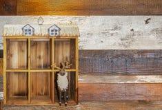 De naald felted Amerikaanse elanden met klokken op tribunes in decoratieve houten schuur met tindak aan één kant van witte achter stock afbeelding