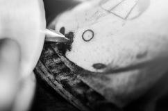 De naald van de tatoegeringsmachine op menselijke huid Stock Foto