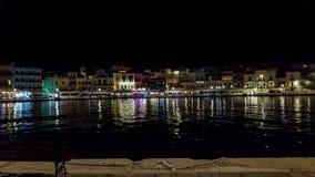 De nacht schoot over Souda-Baai in Chania, Kreta, Griekenland die kleurrijke verlichting van gebouwen en winkels a tonen stock foto