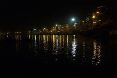 De nacht steekt Varanasi aan diagonaal in het zwarte water van de rivier Ganges, lichte flarden en sporen op het water wordt weer Stock Foto