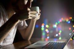 De nachtarbeider in bureauzitting bij de lijst die laptop met behulp van en drinkt koffie F royalty-vrije stock afbeeldingen