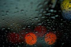 De nachtmening van de stadslichten door het venster in de regen, regen laat vallen het vallen op het windscherm van de auto Samen Royalty-vrije Stock Foto's