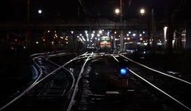 De nachtscène van de spoorweg met blauw verkeerslicht Stock Afbeeldingen