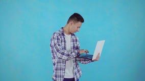 De nadenkende jonge Aziatische mens vindt oplossingen met laptop op blauwe achtergrond in hand stock videobeelden