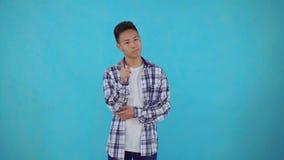 De nadenkende jonge Aziatische mens vindt oplossingen op blauwe achtergrond stock video