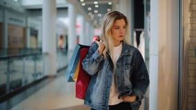 De nadenkende jonge blondevrouw loopt langs een showvenster met zakken in het winkelcomplex stock footage