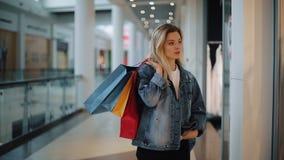 De nadenkende jonge blondevrouw loopt langs een showvenster met zakken in het winkelcomplex stock videobeelden