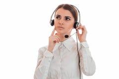 De nadenkende jonge donkerbruine die vrouw van de vraagbeambte met hoofdtelefoons en microfoon op witte achtergrond wordt geïsole Stock Foto's