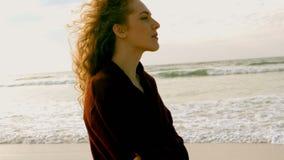 De nadenkende jonge Kaukasische vrouw met wapens kruiste status op strand in de zonneschijn stock videobeelden