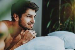 De nadenkende jonge kerel ontspant in bed in ochtend stock afbeelding
