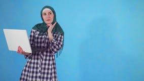 De nadenkende jonge Moslimvrouw gebruikt laptop op blauwe achtergrond stock video