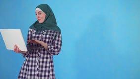 De nadenkende jonge Moslimvrouw vindt een oplossing en gebruikt laptop op een blauwe achtergrond stock video