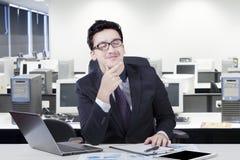 De nadenkende manager veronderstelt iets in bureau Stock Foto