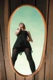 De nadenkende vrouw bekijkt bezinning in spiegel Stock Foto