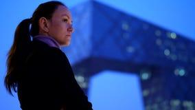 De nadenkende vrouw geniet van moderne cityscape en wolkenkrabber bij nacht stock videobeelden