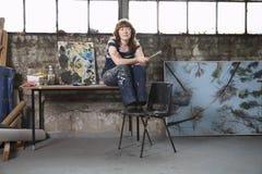 De nadenkende Vrouwelijke Workshop van Kunstenaarswith paintings in Royalty-vrije Stock Afbeeldingen