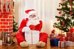 De nadenkende zitting van Santa Claus op de vloer in de ruimte met stock foto