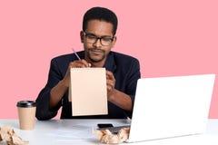 De nadenkende zwarte zakenman probeert om gedicht in notitieboekje voor haar meisje te schrijven terwijl het werken aan laptop Ha royalty-vrije stock afbeeldingen