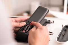 De nadruk op vrouwenhand verandert de het de afstandsbedieningbatterij, reparatie en onderhoud stock foto's