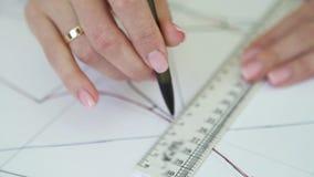 De nadruk van het close-uprek van gehuwde vrouwenhanden die naaiend patroon trekken op papier stock footage