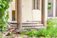 De nasleep beschadigde en ruïneerde villa in de stad van natuurramp, catastrofe of oorlog met gebroken trap stock afbeelding