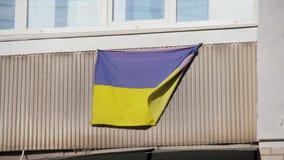 De nationale vlag van de Oekraïne wordt gehangen op balkon van woonhuis stock video