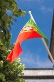 De nationale vlag van Portugal ontwikkelt zich in de wind tegen een blauwe hemel stock afbeelding