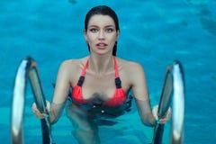 De natte vrouw komt uit water in de pool te voorschijn Stock Foto's