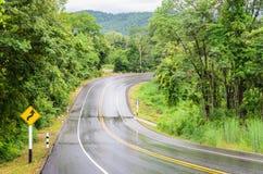 De natte weg van het bergasfalt na regen met verkeersteken van scherp stock foto