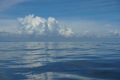 De natuurlijke achtergrondscène van horizon van de gradiënt de blauwe hemel en de pluizige witte wolk boven diep blauw overzees a Royalty-vrije Stock Foto's