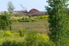 De natuurlijke landschaps dichtbijgelegen stortplaats en het graafwerktuig stock foto's