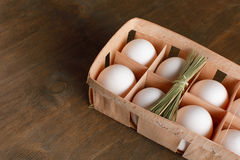De natuurlijke organische kippeneieren in oranje kartonpakket isoleren Stock Afbeeldingen
