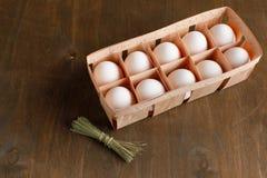 De natuurlijke organische kippeneieren in oranje kartonpakket isoleren Royalty-vrije Stock Foto's