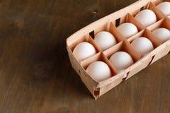 De natuurlijke organische kippeneieren in oranje kartonpakket isoleren Stock Foto