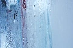 De natuurlijke waterdalingen op glas, vensterglas met condensatie, sterke, hoge vochtigheid, grote dalingen van water stromen ond stock foto