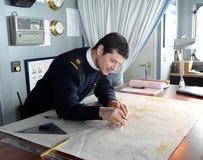 De Navigator van het schip ` via Australis ` die de overzeese route op de kaart van Kaaphoorn bedekken Stock Afbeelding