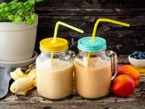 De nectarine van de banaanperzik smoothie in twee kruiken, vers fruitmilksha stock foto's